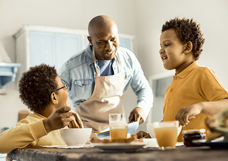 Man and two boys eat breakfast